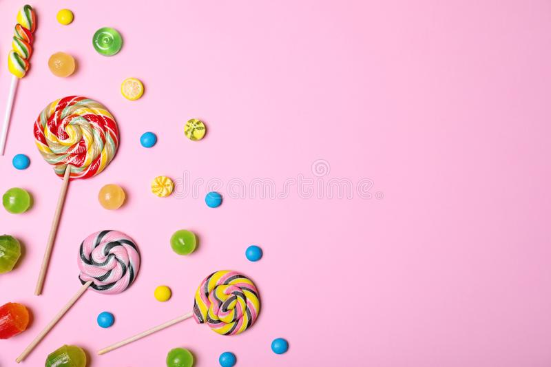 Bright yummy candies and space for text on color background. Top view stock photo