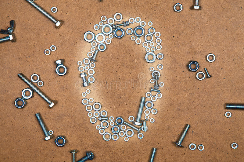 Bright zero from bolts and nuts. Photo of mozaic sign on wood background stock photo