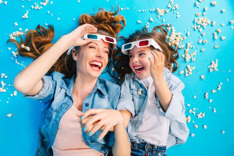 Brightful modieus beeld van hierboven opgewekte moeder en dochter die op blauwe vloer in popcorn leggen, die in 3D glazen lachen royalty-vrije stock afbeeldingen