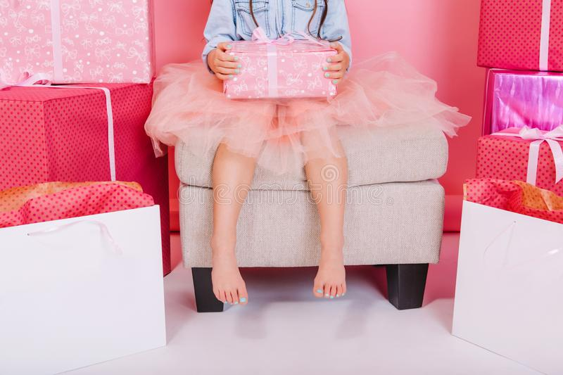 Brightful stylish image birthday present on knees of little cute girl in tulle skirt sitting on chair suround a lot of. Giftboxes. Celebrating happy birthday royalty free stock images
