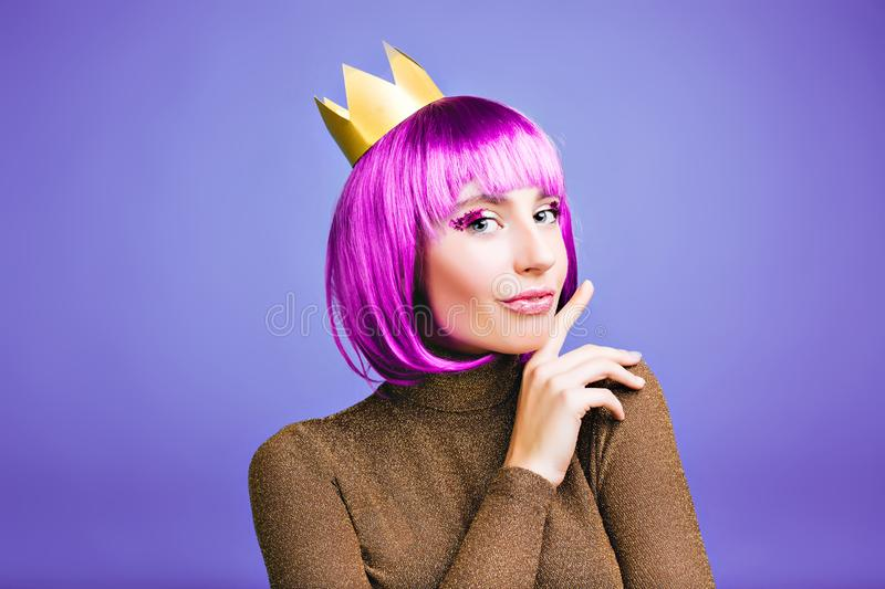 Brightful stylish portrait of charming young woman in gold crown, short purple hair on violet background. Celebrating royalty free stock images