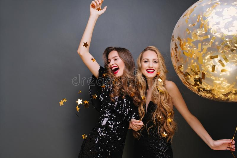 Brightfull expressions of happy emotions of two amazing girls celebrating party on black background. Luxury black stock photos