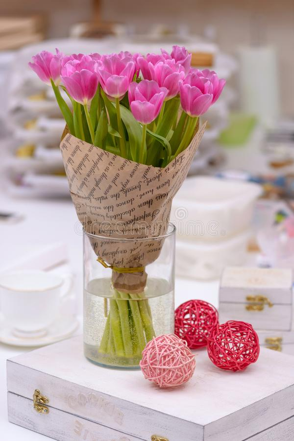 Brightly bouquet tulips in vase on table stock photo