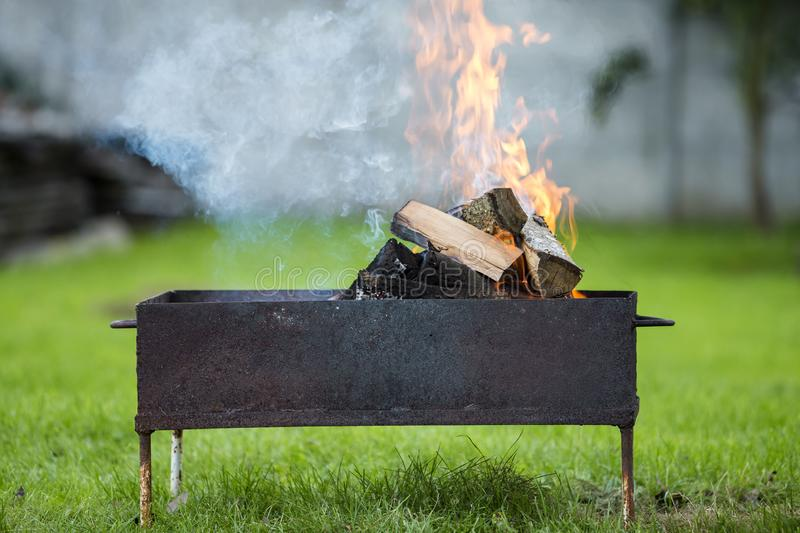 Brightly burning in metal box firewood for barbecue outdoor. Camping, safety and tourism concept royalty free stock image