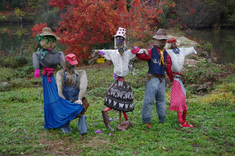 Brightly clothed vintage scarecrows. A group of five scarecrows clothed in brightly colored vintage garments standing in front of an orange tree and small pond royalty free stock photography