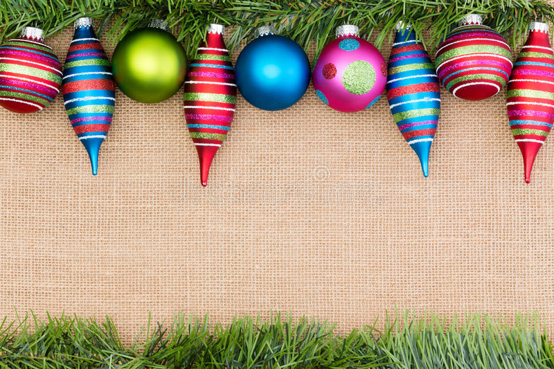 Brightly colored border of Christmas ornaments. Brightly colored border of festive Christmas ornaments, with a garland of green foliage over a textured woven royalty free stock photos