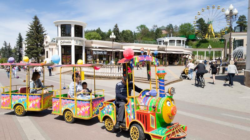 Brightly colored children`s train with young passengers to ride through the pedestrian streets of Kislovodsk royalty free stock image