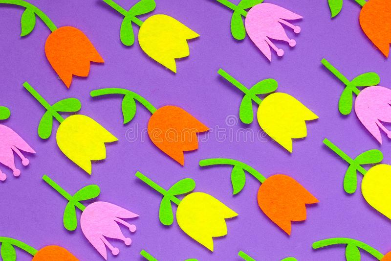 Brightly colored felt tulip flowers on a plain background stock photography