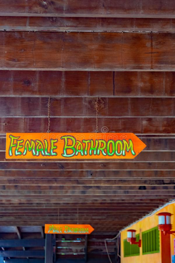 Brightly colored Female and Male Bathroom arrow signs in all caps/capital letters hanging on chain suspended from ceiling. royalty free stock image