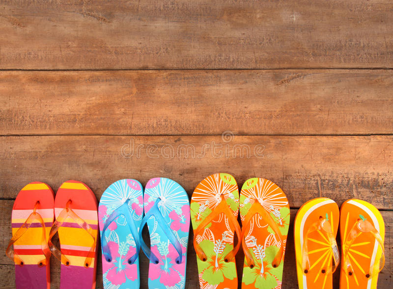 Brightly colored flip-flops on wood stock photos