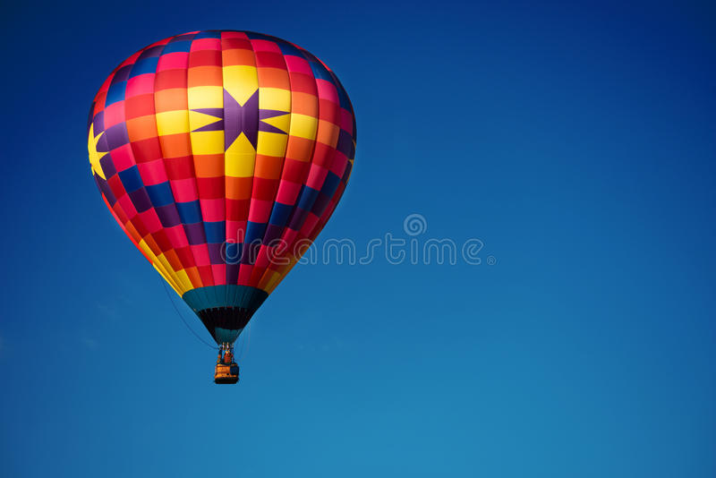 Brightly colored hot air balloon with a sky blue background. A brightly colored hot air balloon with a sky blue background royalty free stock photography