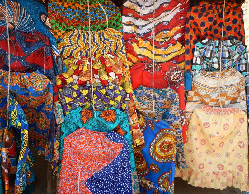 Brightly colored and patterned skirts hanging in merchant stall stock photography
