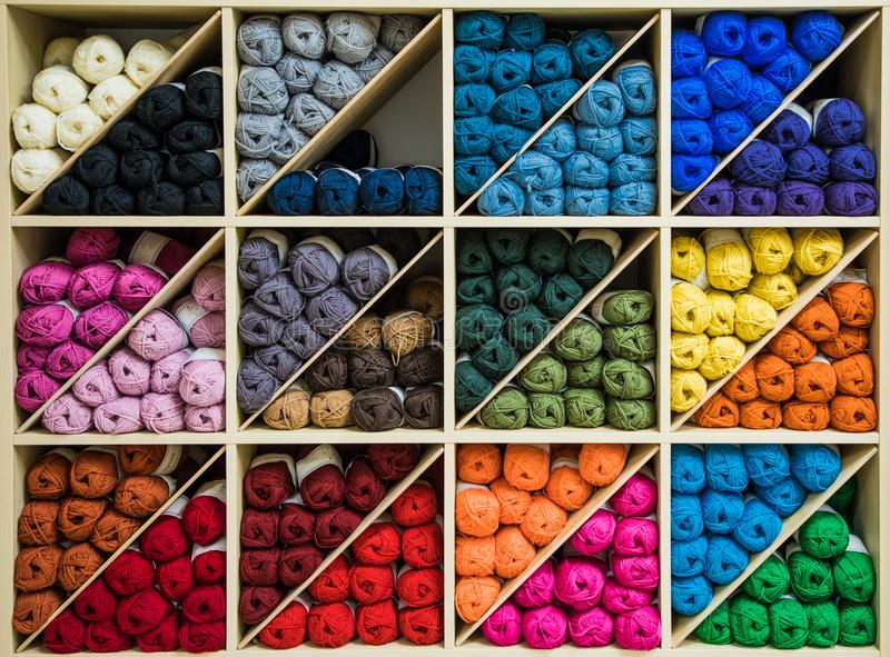 Brightly colored skeins of wool organized by color on triangular shelves royalty free stock photography
