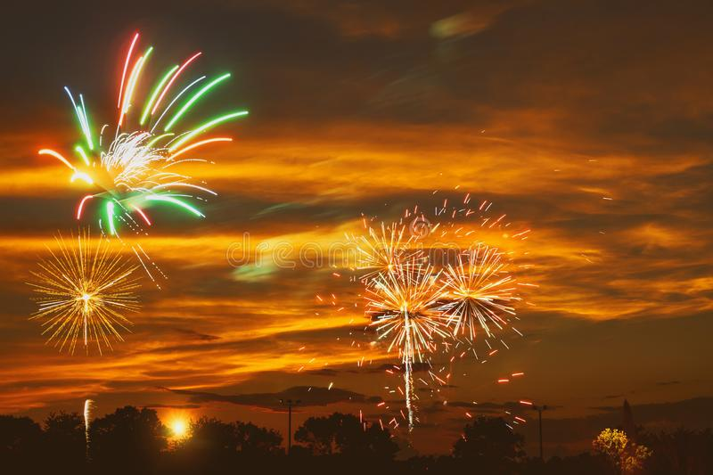 Brightly colorful fireworks in the sunset sky royalty free stock photography