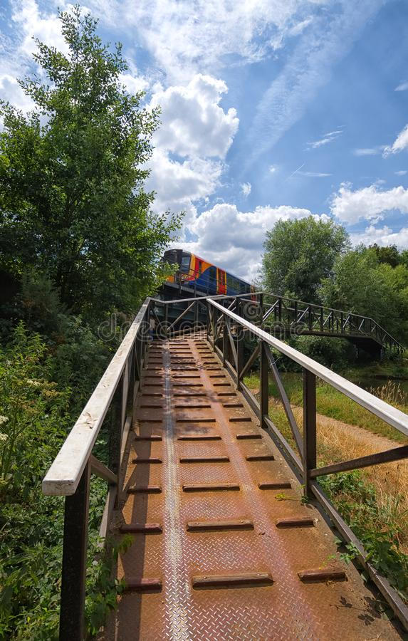 Local Class 450 train crossing bridge over River Wey, Surrey. A brightly coloured class 450 train, crossing a rail bridge near West Byfleet on it`s way to stock photography