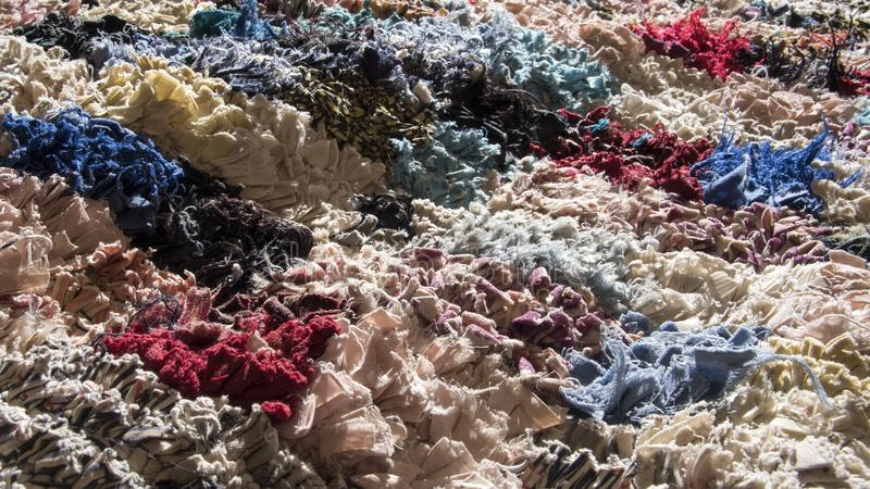 Brightly coloured and heavily textured rag rug in sunlight. Essaouria, Morocco - September 2017: Brightly coloured and heavily textured rag rug in sunlight royalty free stock photography