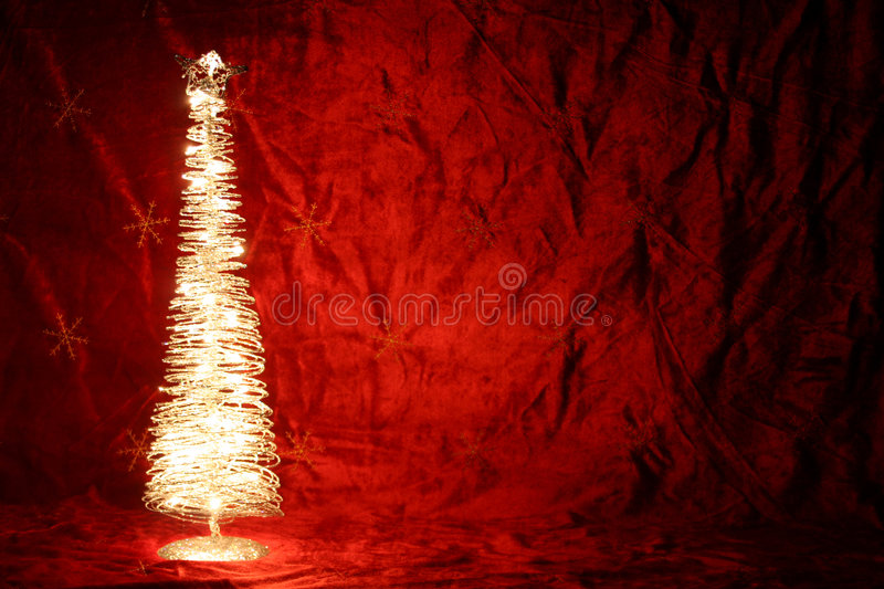 Brightly lit Tree. A background of red velvet with a brightly lit little Christmas tree stock images