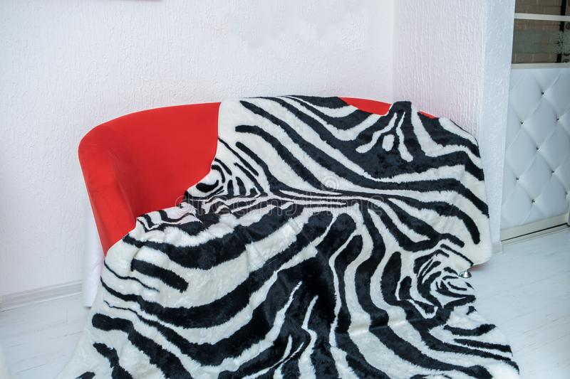 Brightly red sofa with a striped black and white plaid lying on it against a white wall.  royalty free stock photo