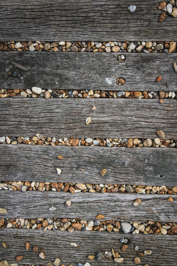 Brighton beach pebbles wooden boards background. Pebbles covering old wooden pathway on brighton beach sussex england stock image