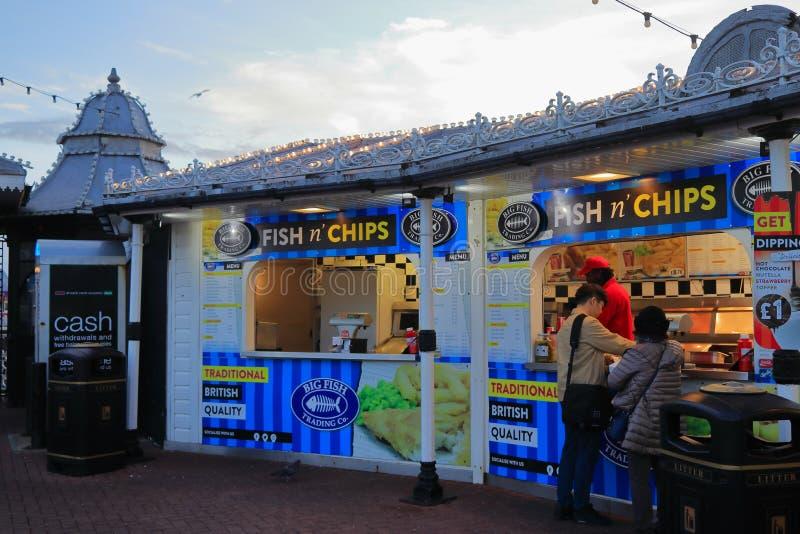 BRIGHTON, EAST SUSSEX, INGHILTERRA, REGNO UNITO - 13 NOVEMBRE 2018: Clienti che comprano l'alimento della via da un pesce e patat fotografia stock