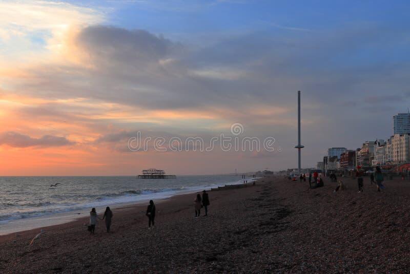 BRIGHTON, EAST SUSSEX, INGHILTERRA, REGNO UNITO - 13 NOVEMBRE 2018: La gente che gode dei colori del tramonto a Brighton Beach fotografia stock libera da diritti