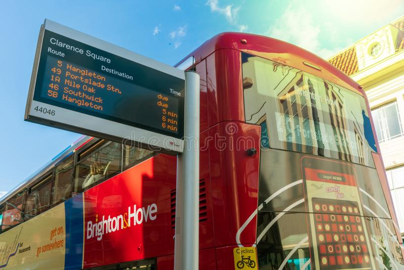 Brighton, England-1 October,2018: Bus stop with digital data boa. Rd information sign for passenger with red two double decker buses in Brighton citytown with royalty free stock photos