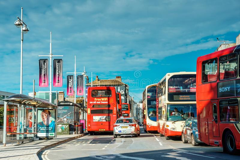 Brighton, England-1 October,2018: Bus stop with digital data board information sign for passenger with red two double decker buses. In Brighton city town with royalty free stock photo
