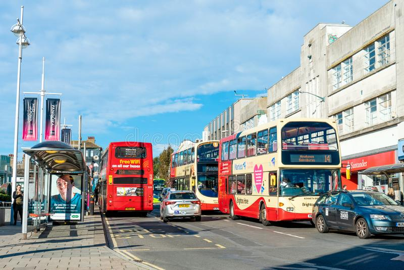 Brighton, England-1 October,2018: Bus stop with digital data board information sign for passenger with red two double decker buses. In Brighton city town with royalty free stock image