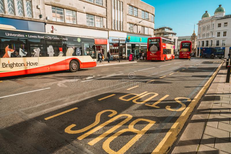 Brighton, England-1 October,2018: Bus stop with digital data board information sign for passenger with red two double decker buses. In Brighton city town with stock photography
