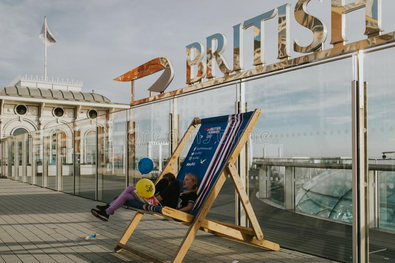 Kids sitting at the base of British Airways 360 lookout in Brighton, UK. stock photo