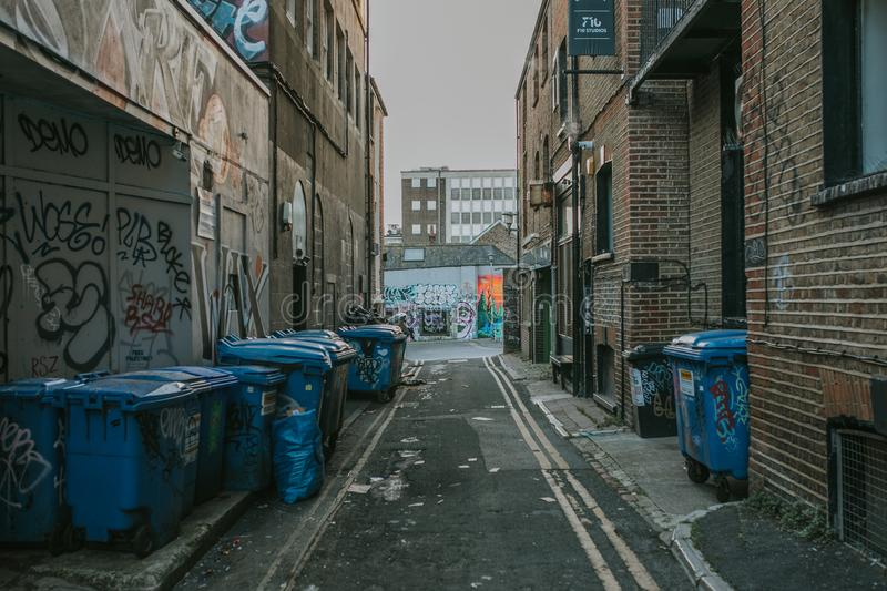 Dirty alleyway in Brighton town, England. BRIGHTON, ENGLAND - October 24th, 2018: Narrow passage way with industrial look, trash, and containers, in Brighton royalty free stock photo