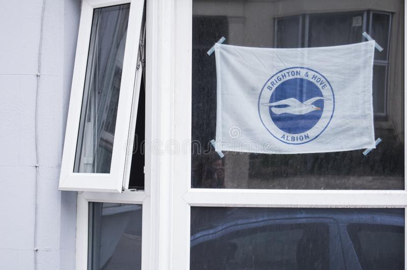 Brighton and Hove Albion. A local resident displays a `Brighton & Hove Albion` flag in their window, taped up at the corners. The logo shows a seagull, the royalty free stock images