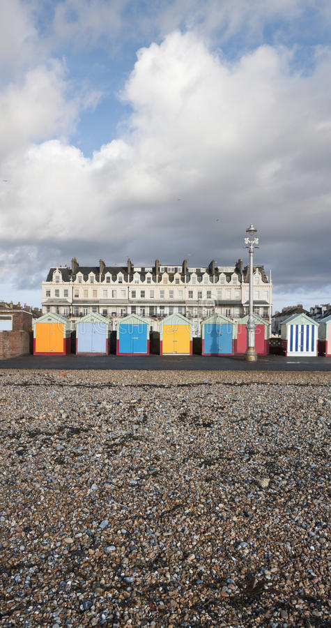 Brighton Hove beach huts along the seafront. Colorful Brighton Hove beach huts along the seafront. Looking from sea back past huts to residence behind royalty free stock photos