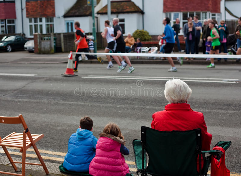 Brighton and Hove marathon. Two childre a senior woman watching the April marathon in Brighton England stock photography
