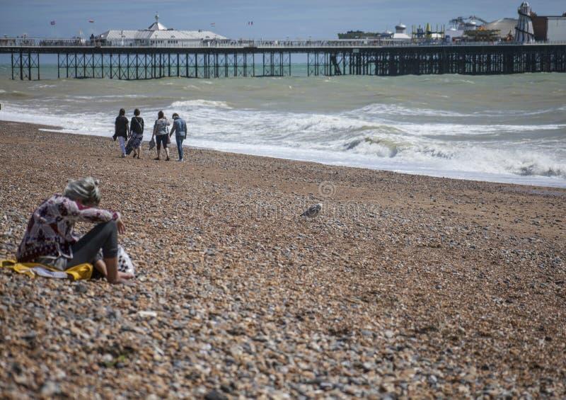 Brighton, Inghilterra - la gente divertendosi sulla spiaggia e sul pilastro fotografie stock