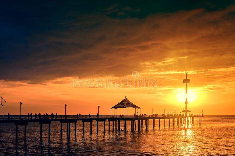 Brighton jetty with people silhouettes. Iconic Brighton jetty with people silhouettes enjoying dramatic sunset, South Australia stock photos