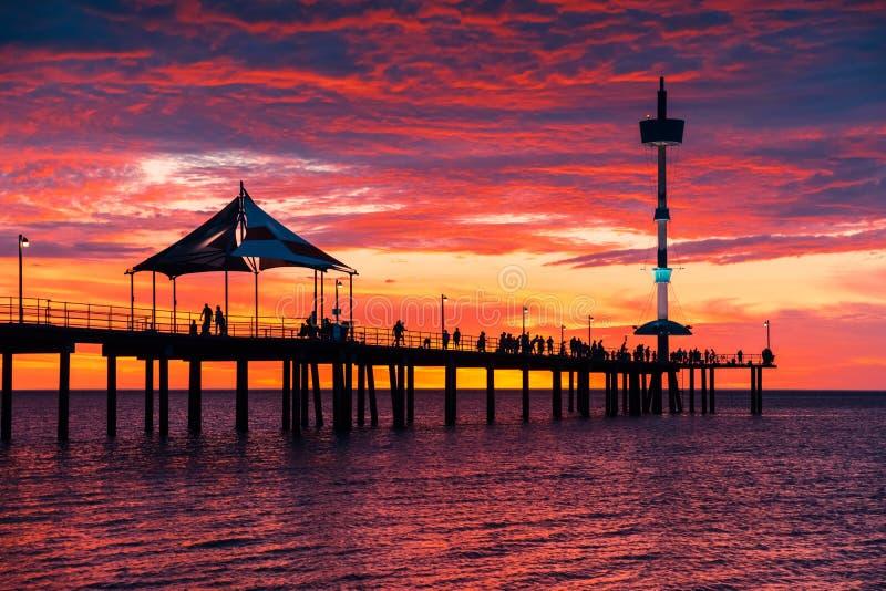Brighton jetty with people at sunset. Brighton jetty with people walking and enjoying sunset, South Australia stock image