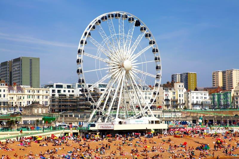 BRIGHTON - JULI 14 - beskådar den guld- sanden av Brighton som är beachfront till det ferrishjulet och nöjesfältet med grupp männ arkivbild