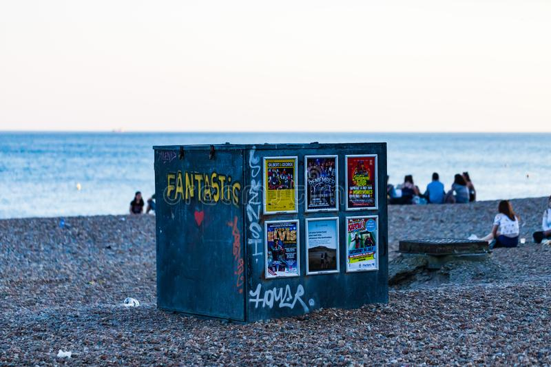 Brighton, UK - June 2018 Adjustable Deck Chair Storage in Brighton Beach England. Seats For Hire Container Standing on. Pebbled Shore. People Sitting and stock image