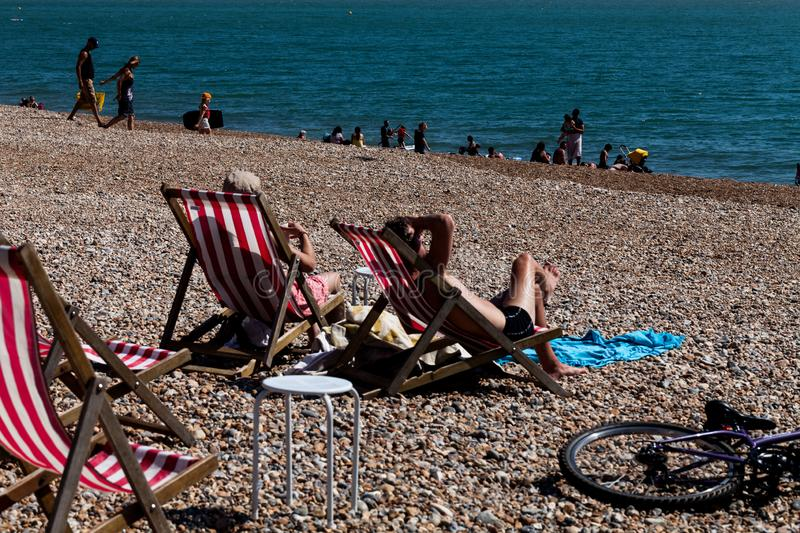 Brighton, UK - June 2018 Couple Relaxing on Wood Adjustable Recliner under the Sun. Family and Group Enjoying Blue Water. And Sunshine. Deck Chairs on Pebbled stock photography