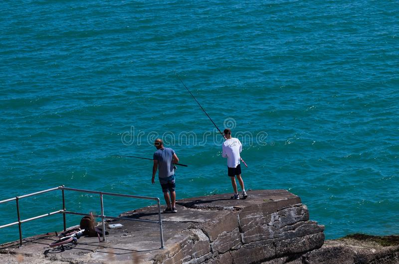 Brighton, UK - June 2018 Two Men Standing on Rock Ashore Holding Fishing Rod. Wavy Crystal Blue Water on Sunny Day royalty free stock photos