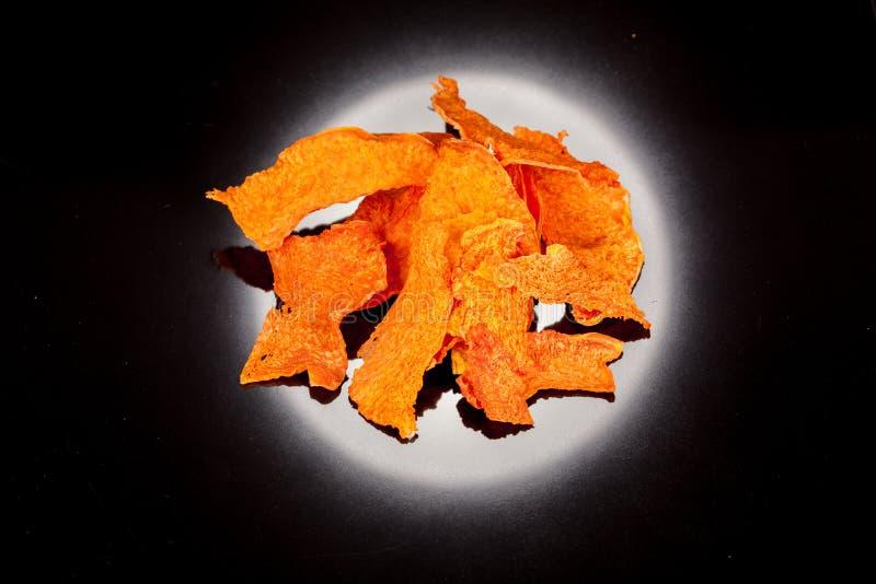 Brilhante, laranja, petisco crocante, torrado da abóbora madura e doce em um backgroun preto foto de stock