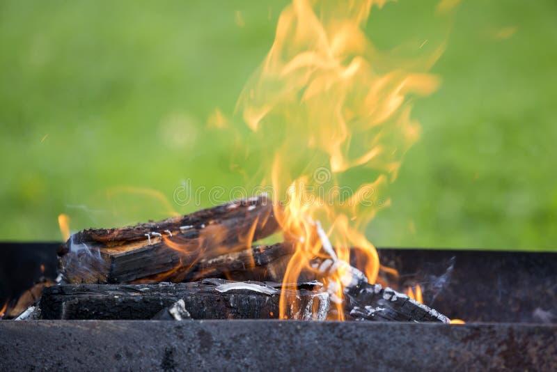 Brilhantemente queimando-se na lenha da caixa do metal para o assado exterior Conceito do acampamento, da segurança e do turismo fotos de stock