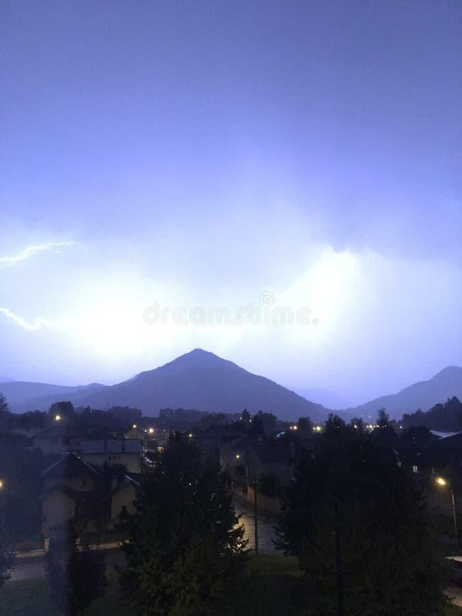 Brilho e temporal acima da montanha e da cidade fotos de stock royalty free