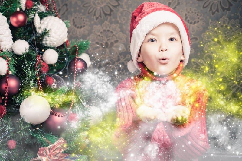 Brilho mágico feericamente de sopro feericamente do rapaz pequeno, stardust no Natal imagens de stock