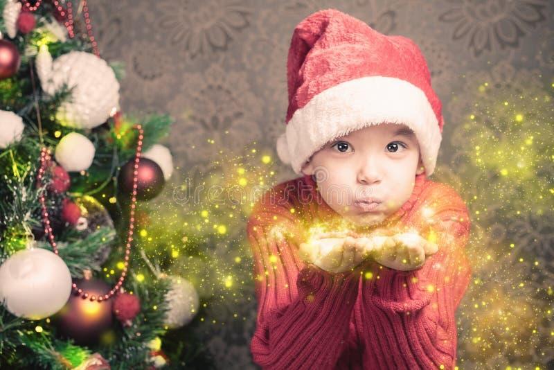 Brilho mágico feericamente de sopro feericamente do rapaz pequeno, stardust no Natal imagem de stock royalty free