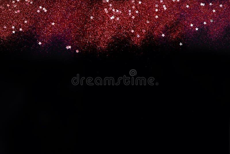 Brilho vermelho com as estrelas no fundo abstrato preto para Valentim, aniversário, aniversário, casamento, o ano novo e o Natal fotos de stock