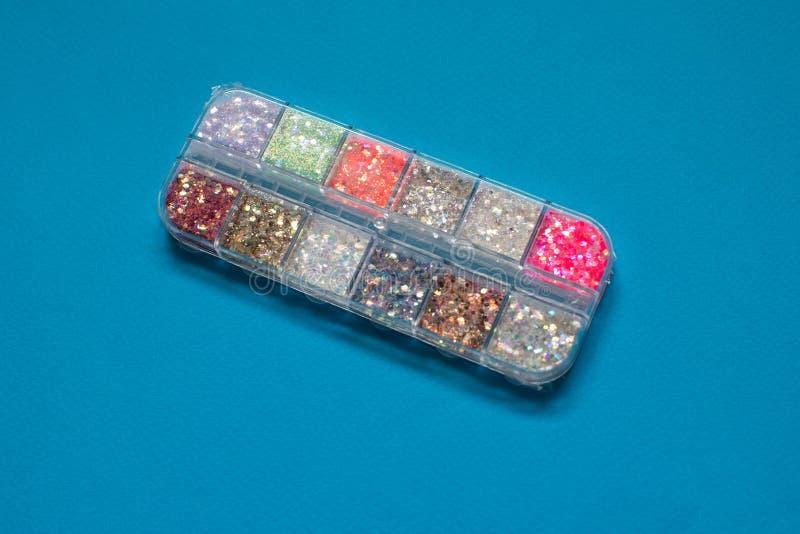 Brilhos coloridos para a arte e a composição do prego no recipiente pequeno no fundo azul imagens de stock