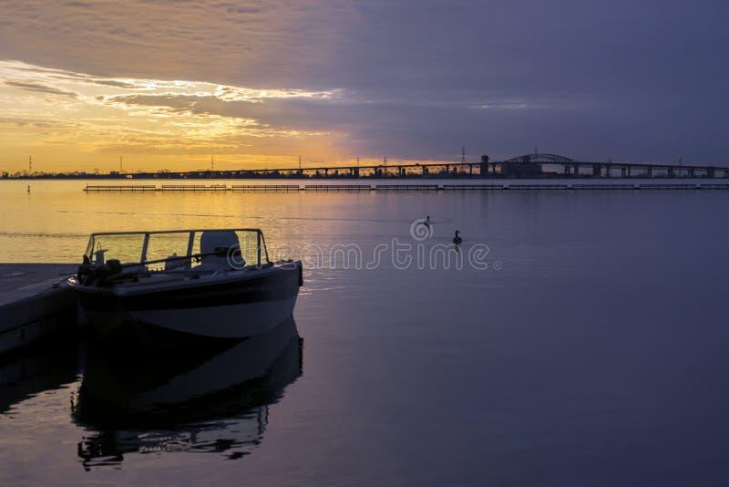 Briljant guld- och violett soluppgång över lugna vatten, rekreation royaltyfria foton