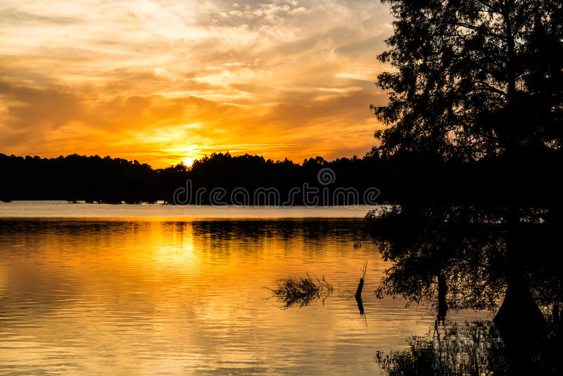 Briljant orange sol på skymning på den knubbiga sjön arkivfoton